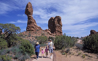 a family walks on a sidewalk with a balanced rock in the background