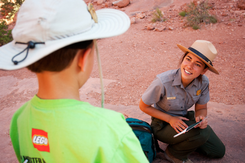 a kneeling park ranger smiles at a child