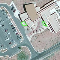 a satellite image showing building with two green outlined areas outside the building