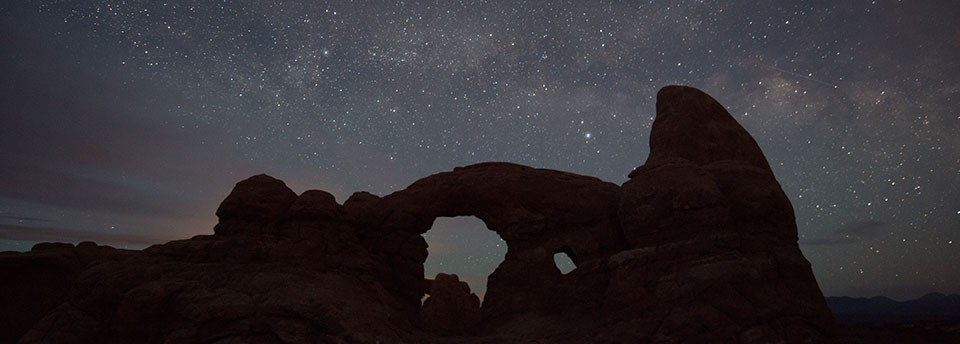 stars above a silhouetted Turret Arch