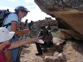 a park ranger with visitors under a rock alcove