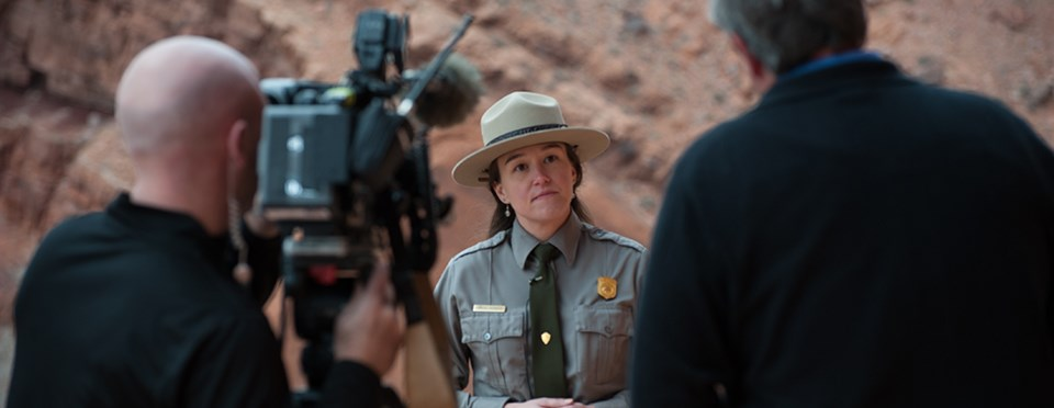 a park ranger stands in front of a video camera
