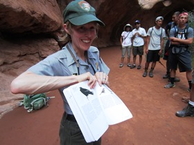 smiling ranger displaying open field guide