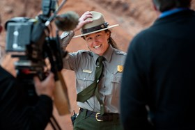 a smiling park ranger hanging on to her hat