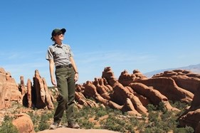 a park ranger with red rock fins in the background