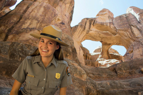 a park ranger with the two holes of Skull Arch behind her
