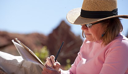 a woman wearing a pink shirt and straw hat holds a paintbrush.