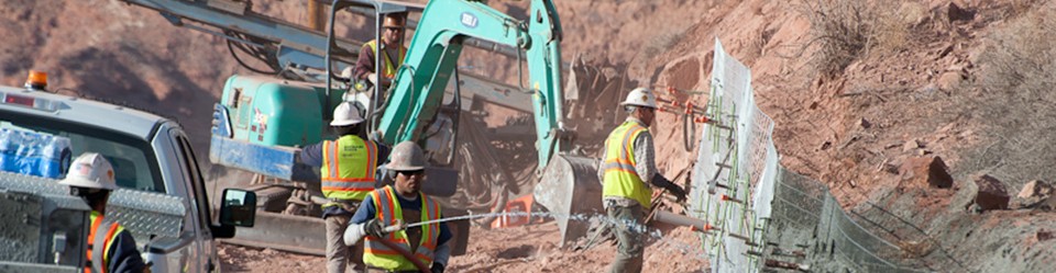 construction workers and a green backhoe at a construction site