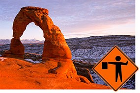 A road construction sign superimposed on a photo of Delicate Arch