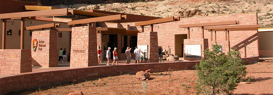 people look at exhibits mounted on red stone walls outside a reddish stone building