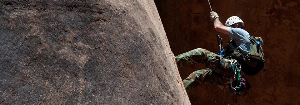 A man in a helmet rappels down a rock face