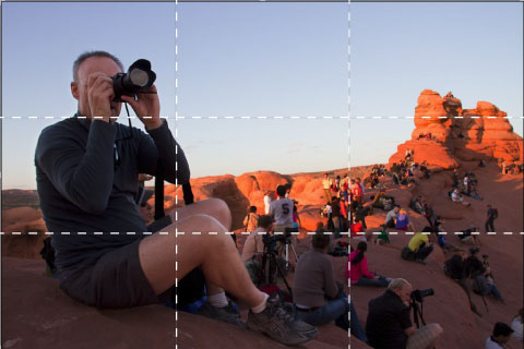 A photographer points his camera. A white grid is superimposed over the photo.