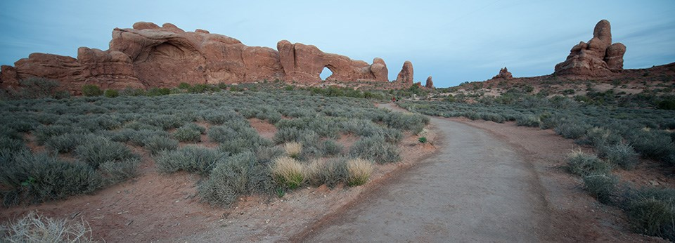 a hard trail leads to a large stone arch
