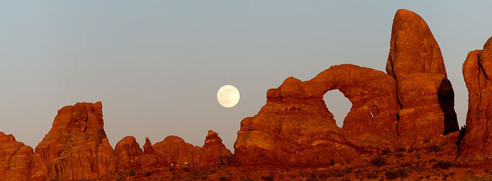 a large, stone arch with the full moon rising above it