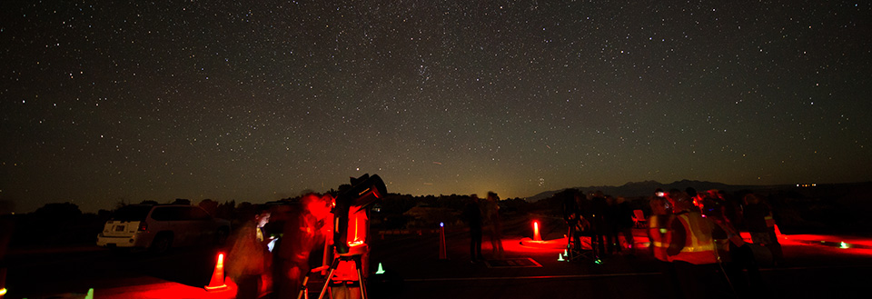 People and a telescope illuminated in red, with stars overhead