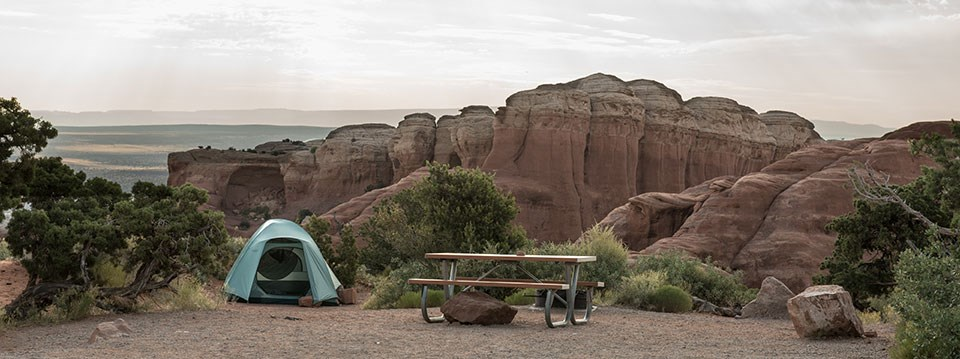 a tent and picnic table at a campsite, with red rock cliffs in the background