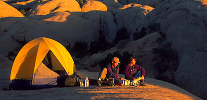 Backpackers prepare a meal as the sun sets.