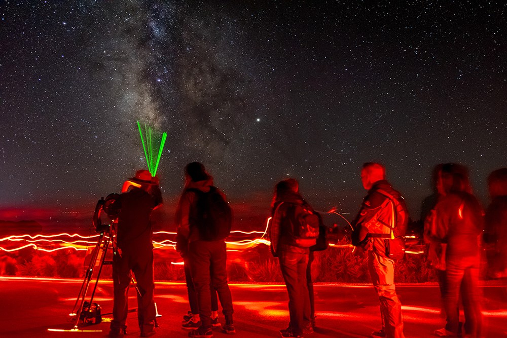 a ranger at a telescope uses a green pointer to show something in the starry night sky to a line of people.