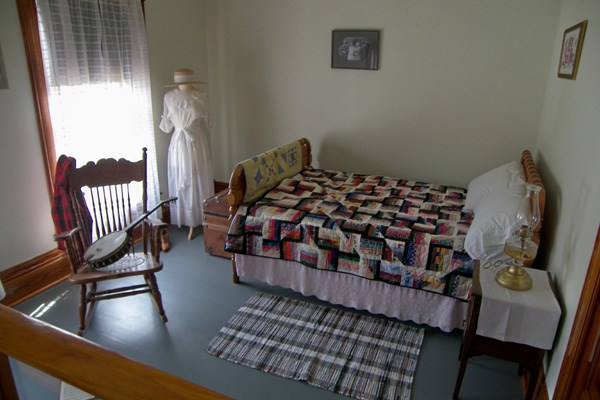A full size bed covered with a colorful quilt, a rocking chair with a banjo on it, and a white dress hanging up in the corner.
