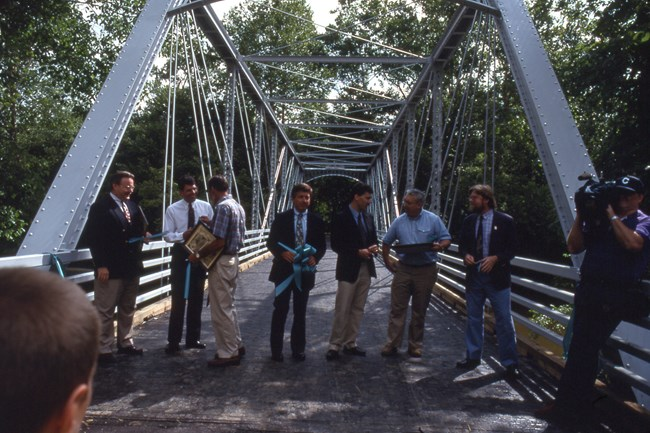 Seven men stand in a line across the bridge, chatting and holding plaques and cut ribbon with a TV cameraman, right.