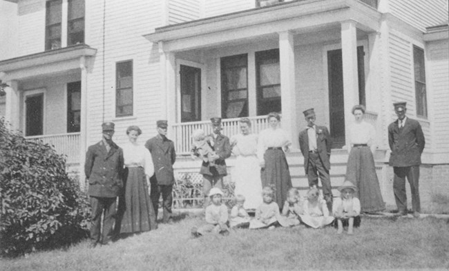 A black and white photo of 5 men in dark uniforms, 4 women in white blouses, and 7 children in the 1920's posing in front of a white house.