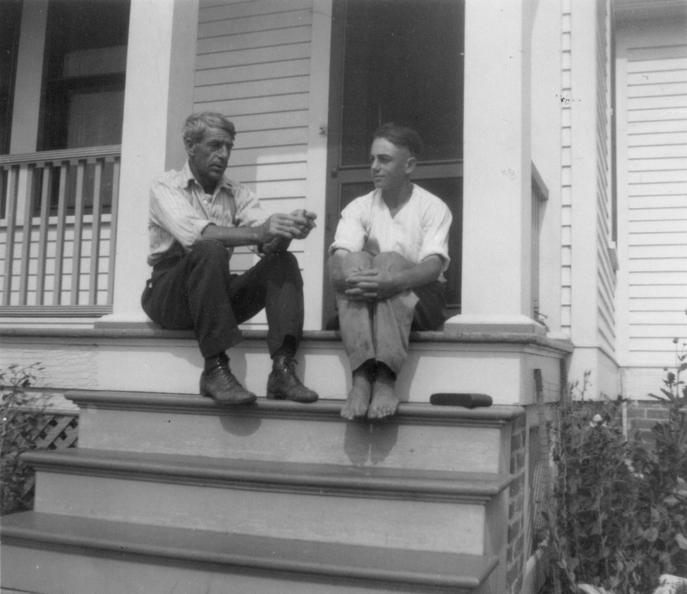 A father and teenage son sit on the front steps of a white house barefoot.