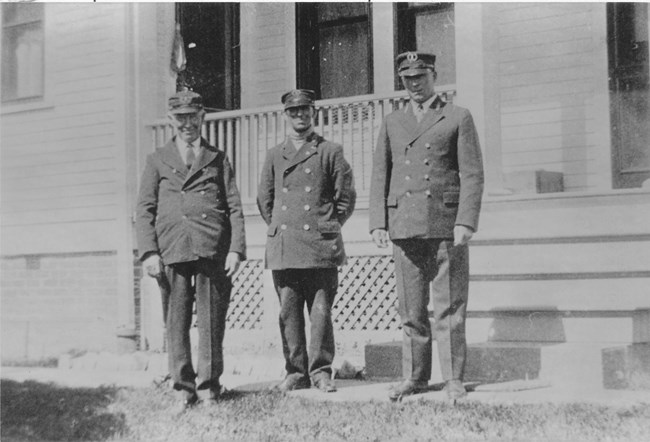 A black and white photo of three men standing in front of a house wearing a dark uniform with hats.