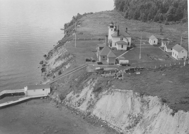 An aerial view of a white lighthouse on the steep shore of a lake, barn, fog signal building, lawn, and stairs leading down to a dock in the lake.