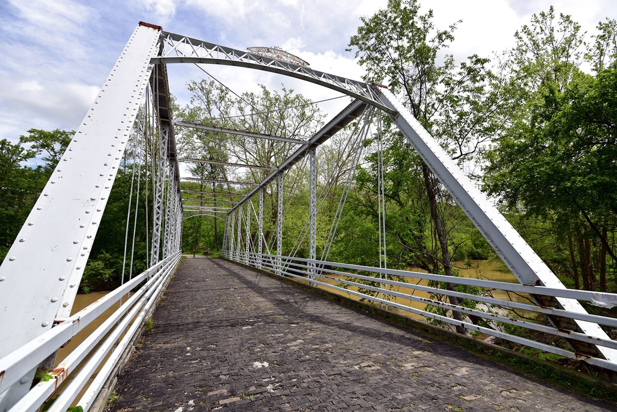 View down a rusting white metal truss bridge with a wooden floor spanning a muddy river.