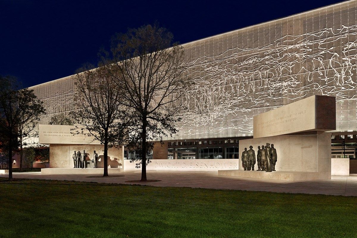 A large metal tapestry hanging over memorial statues of Eisenhower at night