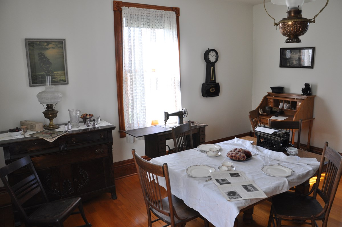 A dining room table set with plates, cups, a pie, and type writer. An antique Singer sewing machine in the back ground and clock on the wall.