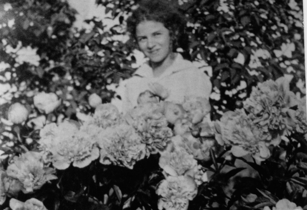 A black and white photo of a woman smiling behind a mound of flowers.