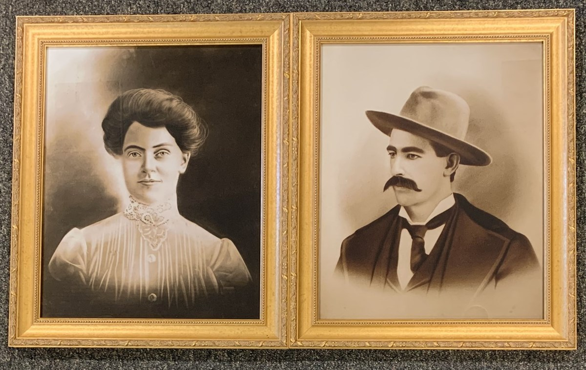 Two framed portraits of a woman on the left in a white blouse with her hair pulled up and a man on the left wearing a hat with a thick mustache.