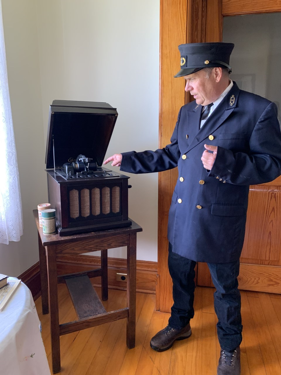 A man dressed in a black lighthouse keeper uniform pointing towards an Ambrola music machine.
