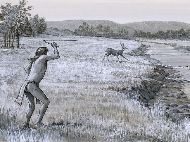 Dressed in a loincloth, the man holds the atlatl above his head. At one end balances the end of the spear, forming an elbow-shape.