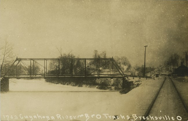 Side view of a metal truss bridge over a frozen river blanketed in snow with railroad tracks and small buildings, right.
