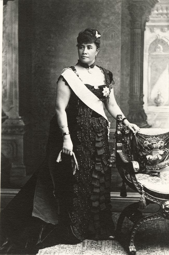 A woman standing next to a chair. She is wearing a sash.