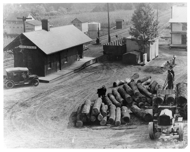 Four men stand on logs being unloaded from a truck with metal tires. A car is parked by a depot along railroad tracks with a cornfield beyond.