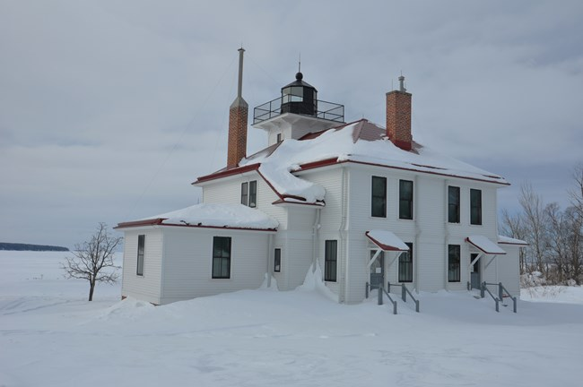 A white lighthouse station with red trim covered in snow.