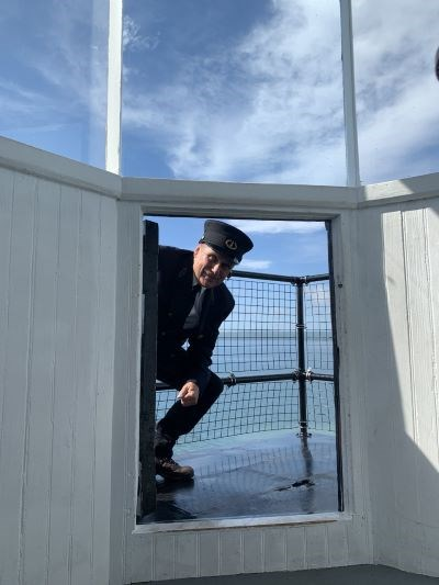 A man dressed in a black lighhouse keeper uniform crouched at the top of the small door leading out to the top of the lighthouse platform.