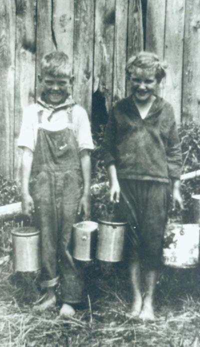 A black and white photo of two children, a boy and girl, standing  barefoot in front of a wooden fence holding buckets of berries in each hand.