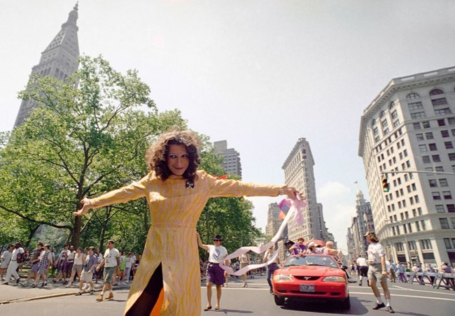 Sylvia Rivera is standing in the streets of NYC in a yellow dress in front of a red car