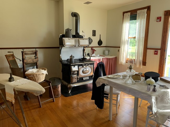 An example of a kitchen in the 1920's with an ironing board, laundry basket, black metal wood fired stove, and a table set with dishes and a lantern.