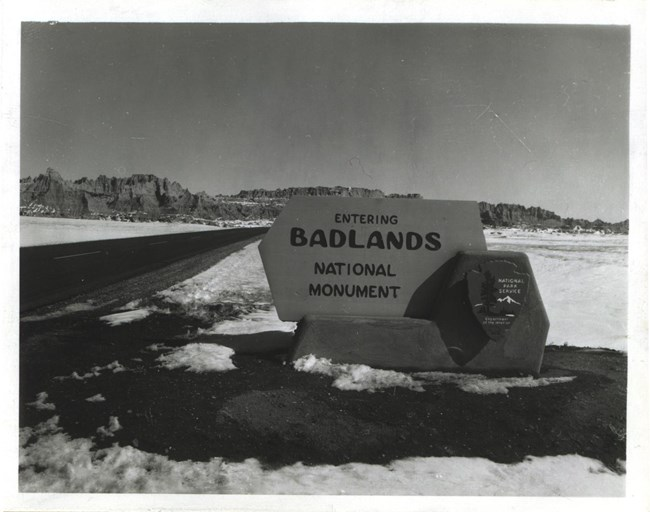 "a historic black and white photograph shows the original park sign reading ""entering badlands national park"""