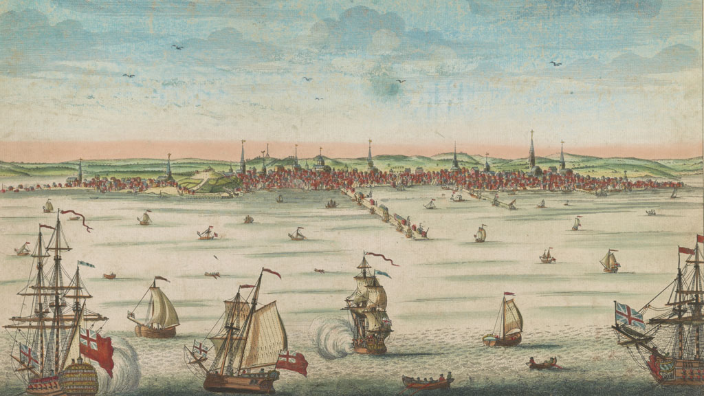 Colored engraving print of a wide harbor with many different ships sailing. Some are firing cannon as evidenced by a plume of smoke. In background is a large harbor town with many steeples pointing above the low houses. In center a long wharf protrudes from town toward viewer into the harbor.