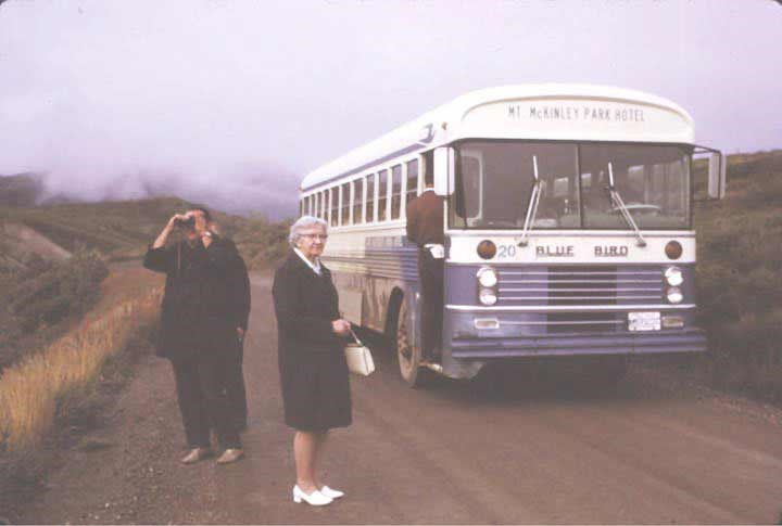 two women standing outside of a blue and white bus with marquee reading mount mckinley park hotel, on a dirt road