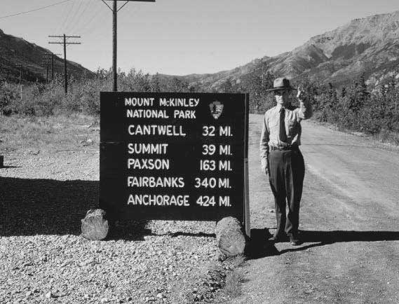 uniformed park ranger standing next ot a sign that reads mount mckinley national park and mileages to locations in alaska