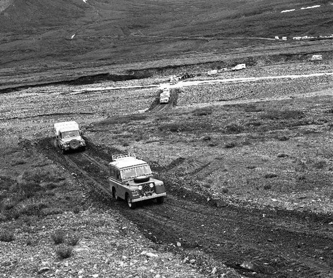 vehicles driving on a narrow gravel road in a tundra meadow