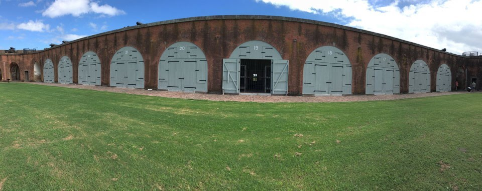 panoramic view of fort wall open casemate with iron bars flanked by closed casemates
