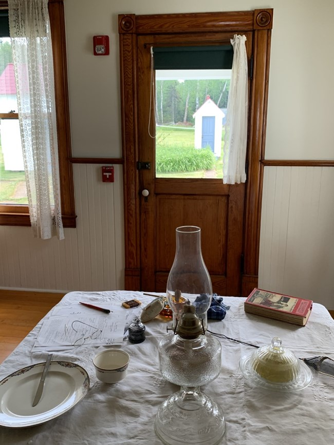 A kitchen table set with a white table cloth, dishes, lantern, and book looking through a glass window at a small outside outhouse.